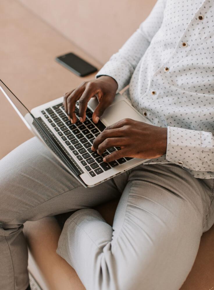 Junger Mann benutzt sein Macbook um Produkte und Dienstleistungen Online zu finde.