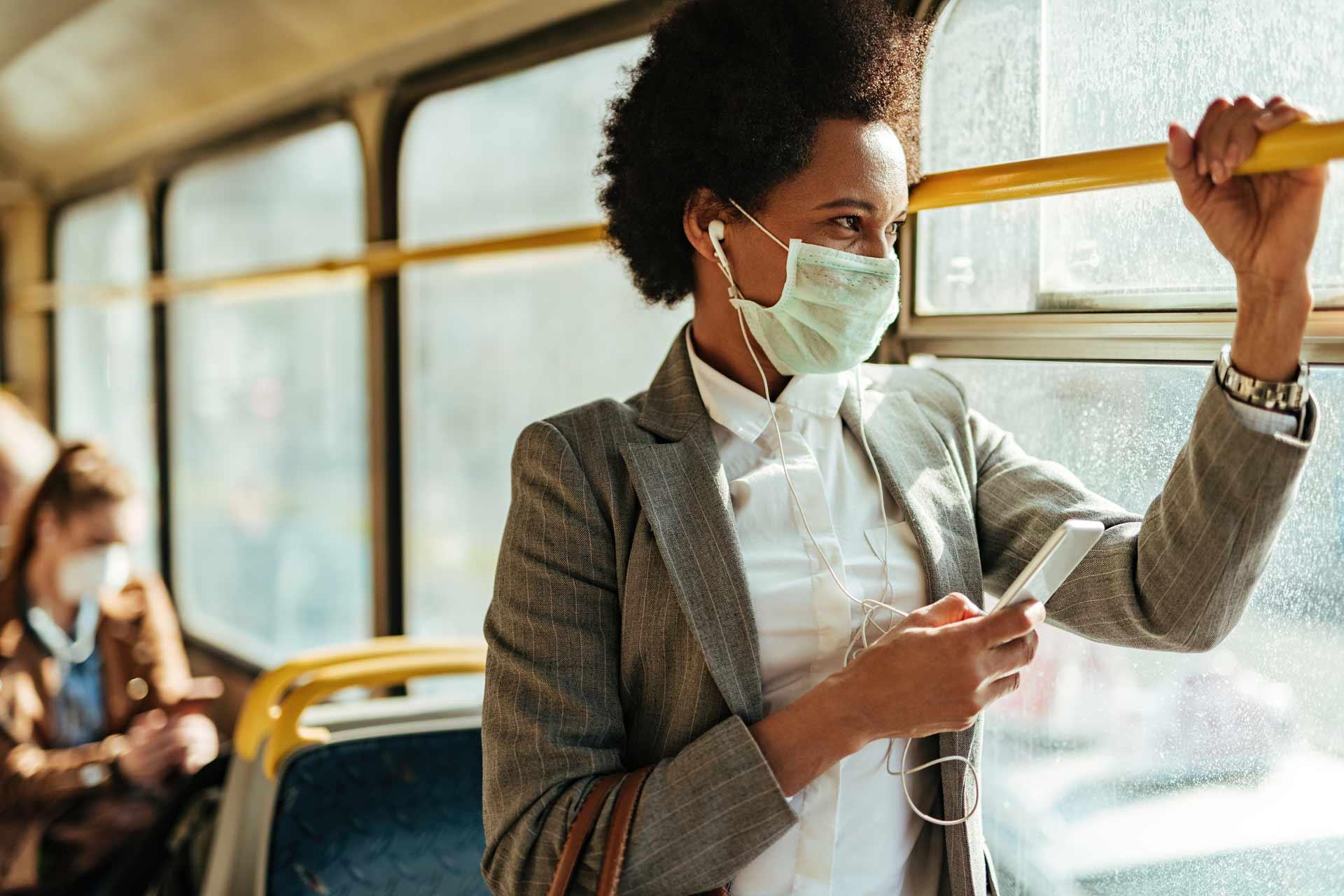 Junge Frau mit Smartphone und Maske fährt mit dem Bus von der Arbeit nachhause.