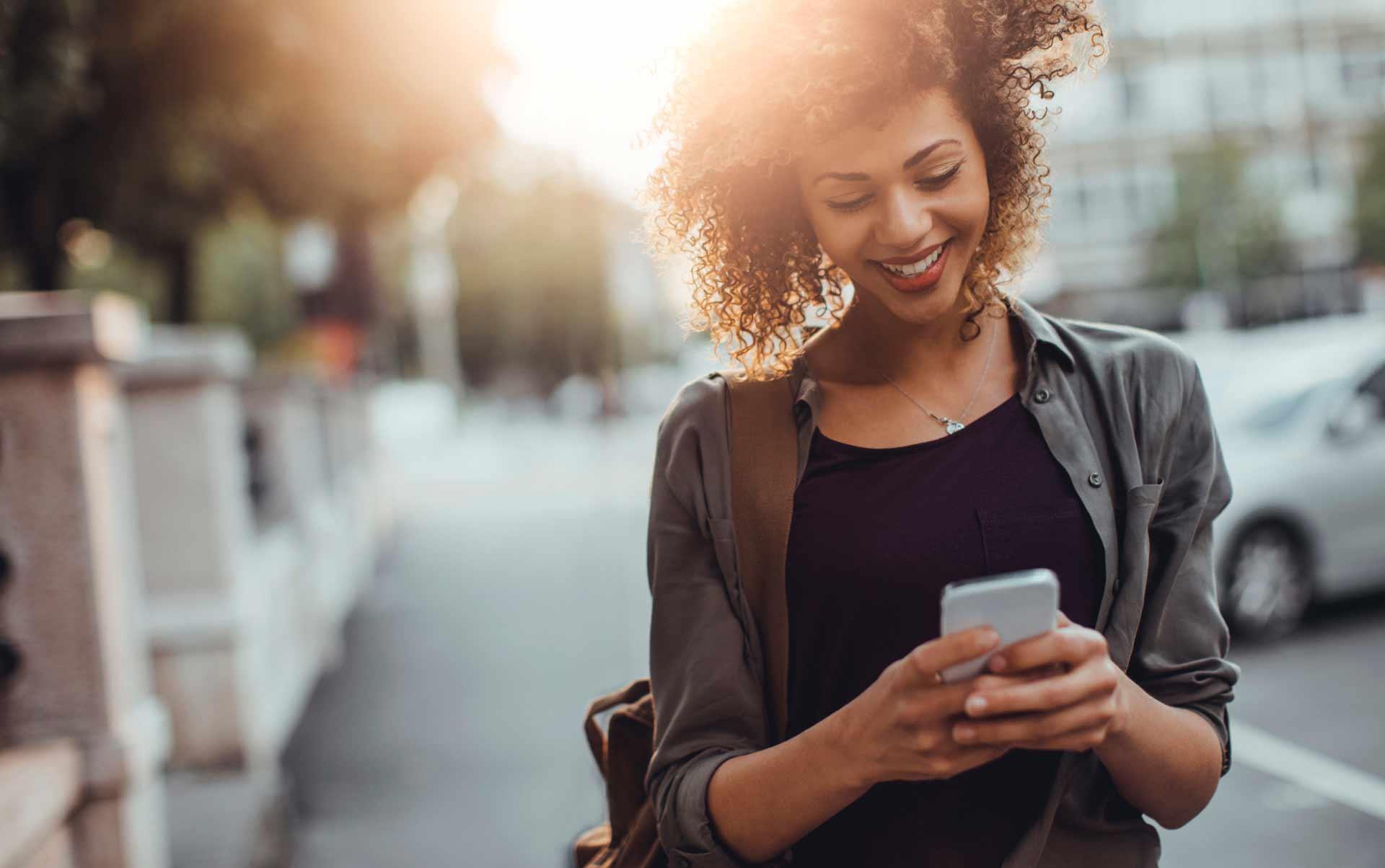 Junge Frau besucht Webseite mit Ihrem Mobiltelefon