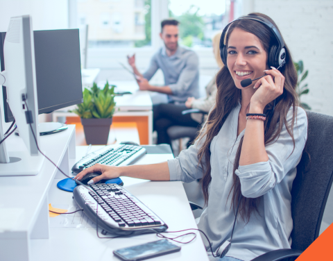 Call center agent smiling while talking on the phone