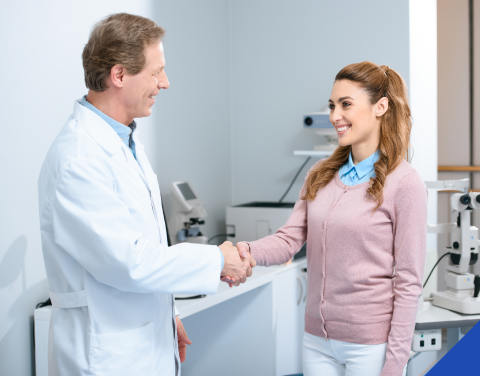Doctor and patient smiling and shaking hands