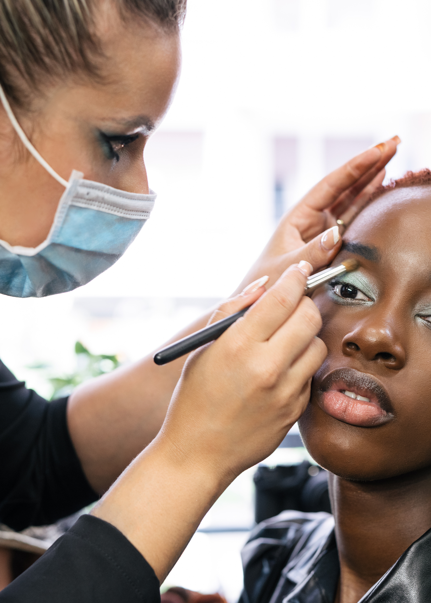 Doing makeup at a salon, with face mask on