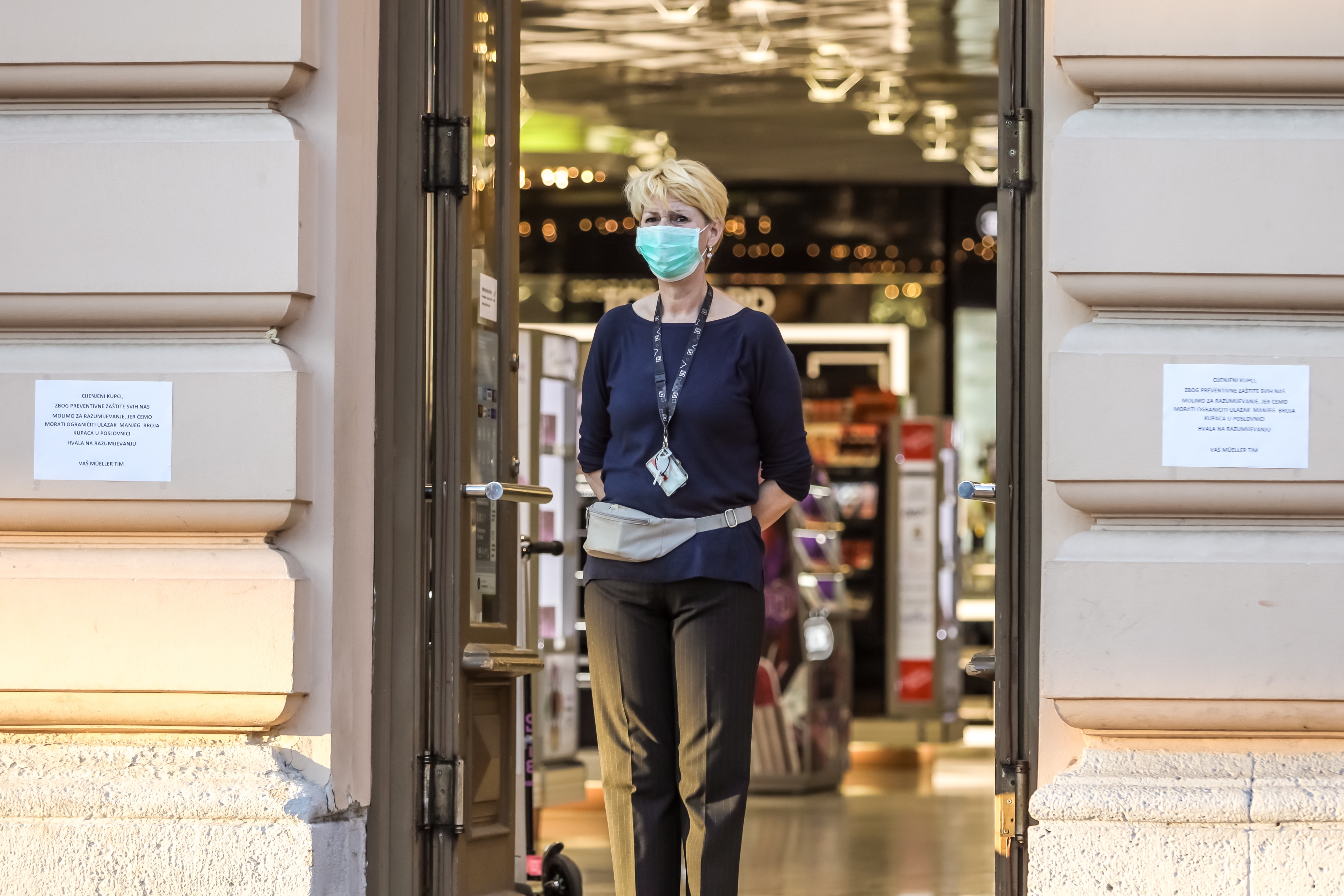 Woman wearing a mask in front of store