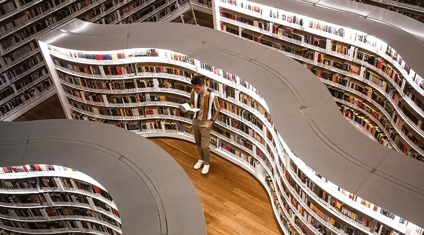 Man standing in rows of bookshelves holding book