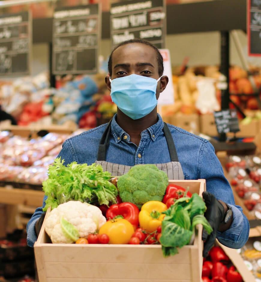 Grocer holding a basket of fruit