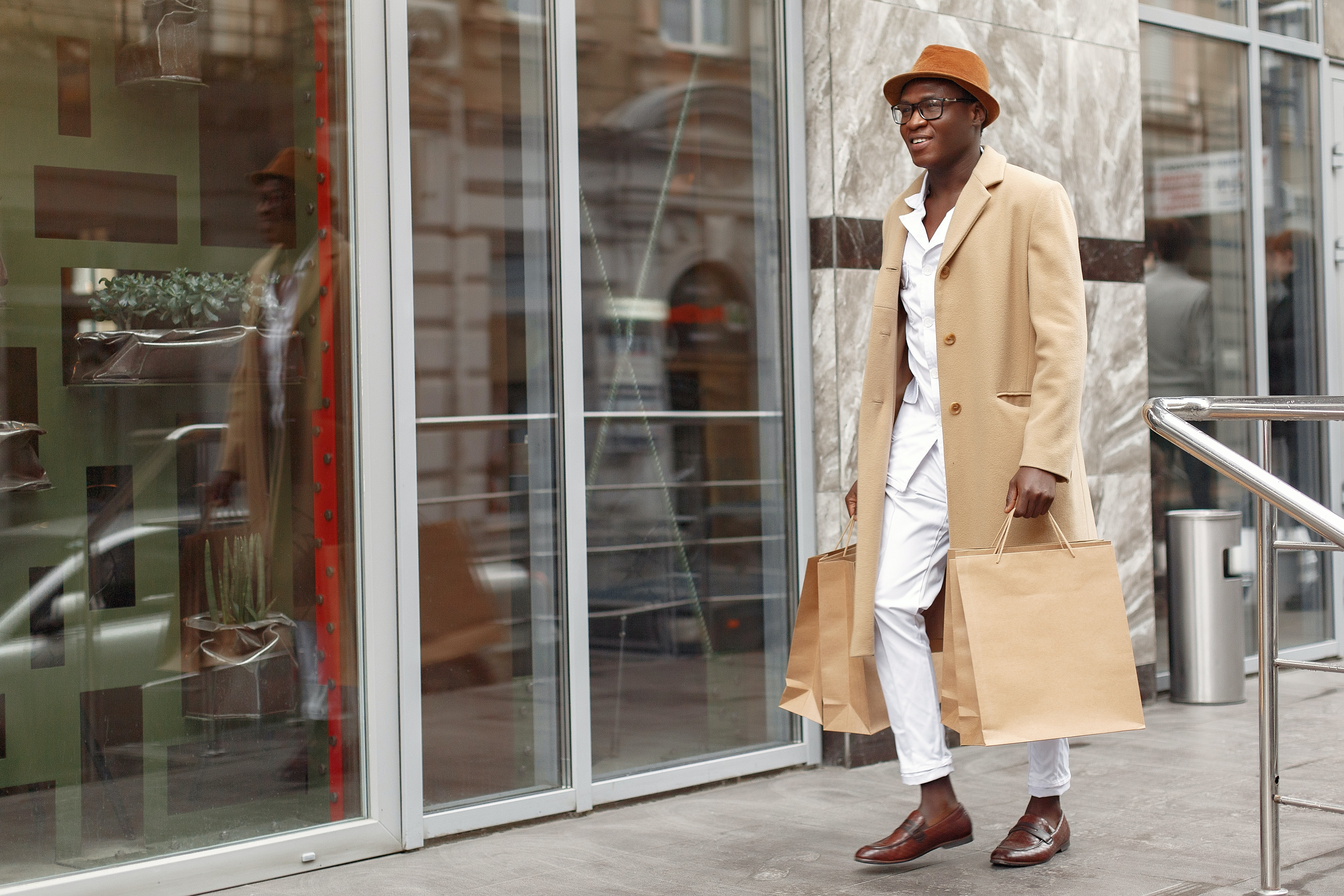 young fashionable man with shopping bag walking into a store