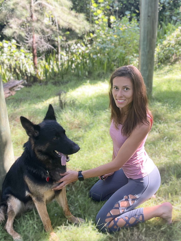 Sophie sitting outside next to her German Shepherd wearing the Healbe GoBe 3 fitness tracker.