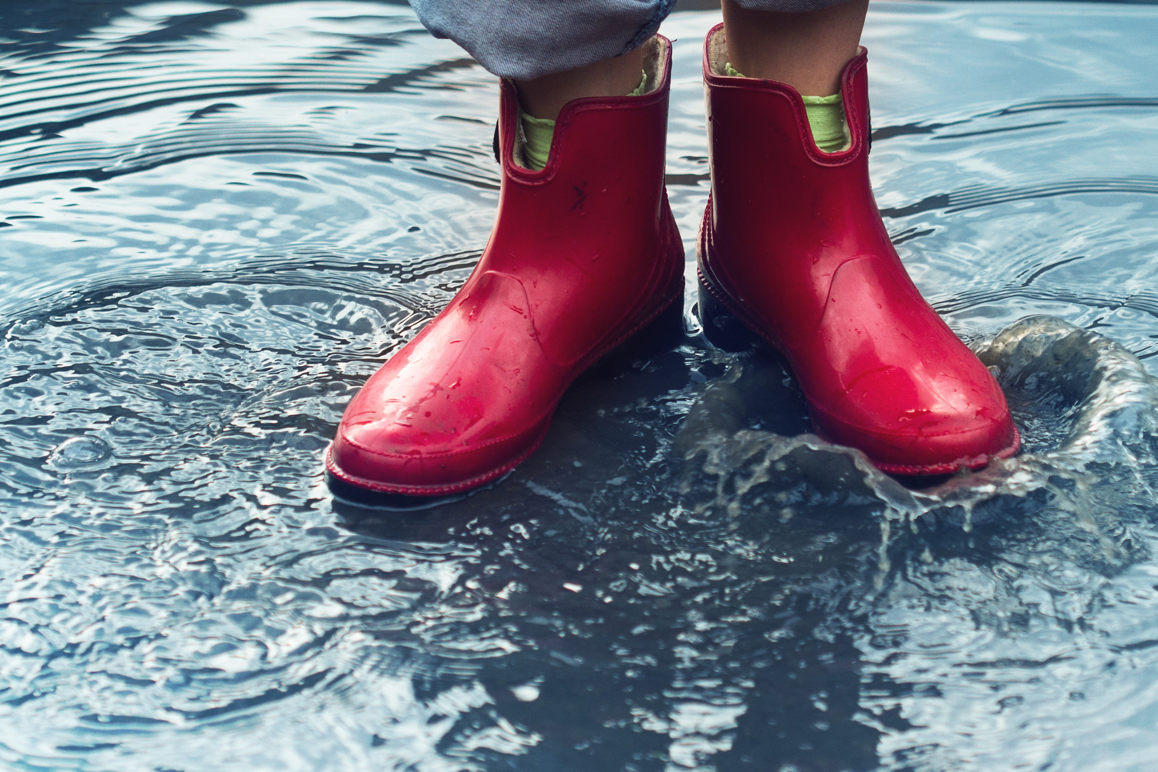 A bright red rain boots standing over a puddle of water
