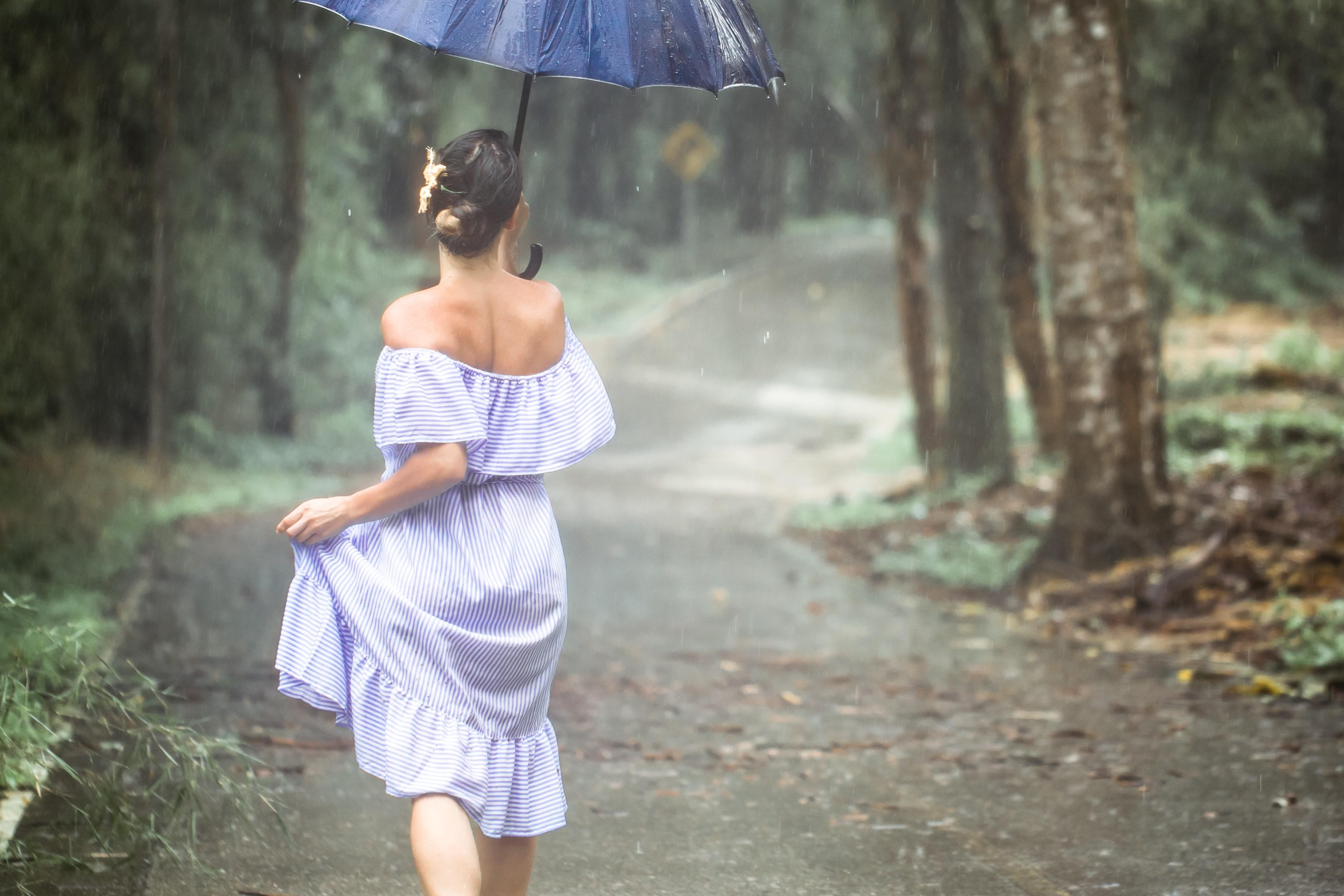 Woman wearing purple stripe dress holding a blue umbrella