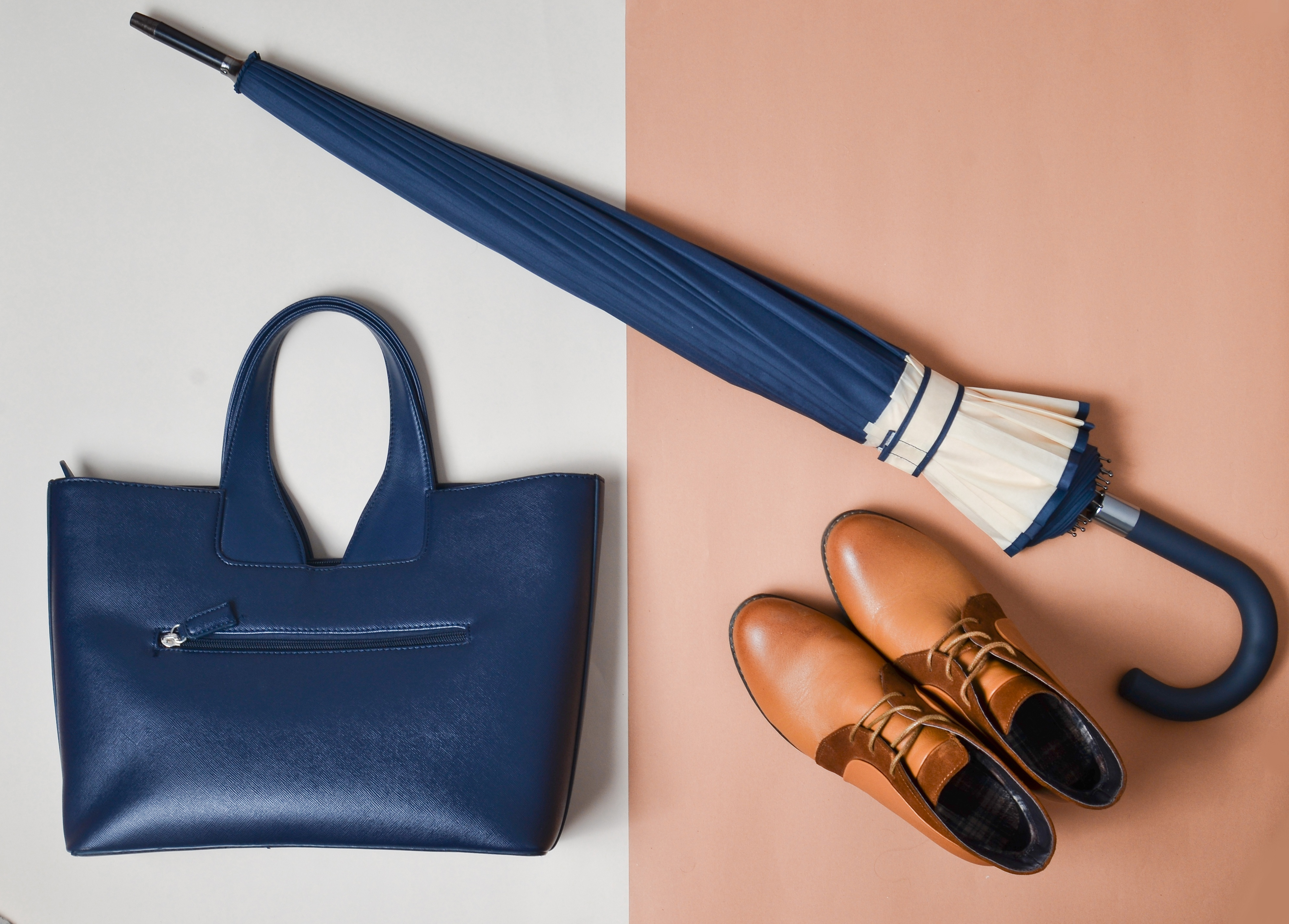 A flat overlay image of a blue bag and umbrella with brown leather boots