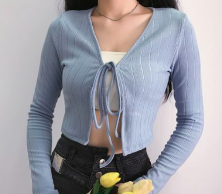 Woman wearing a blue lightweight knit over a white tube top