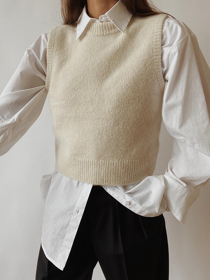 Cream sweater vest over white shirt