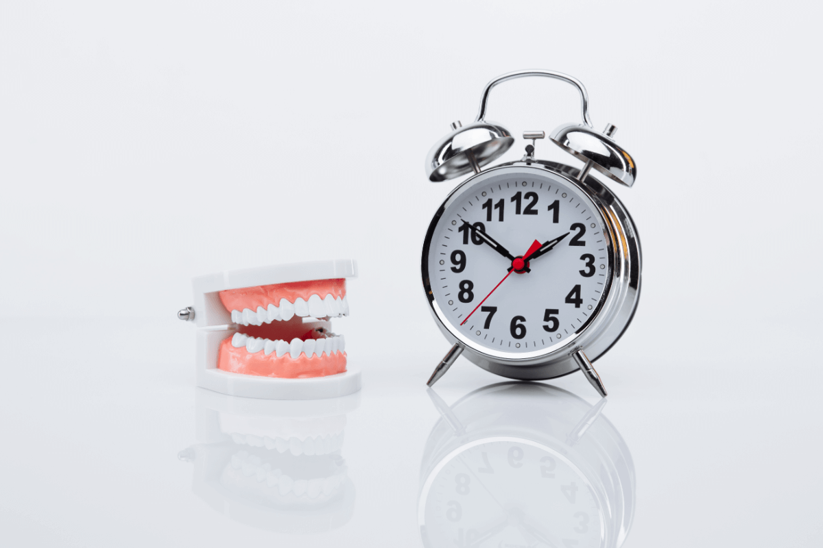 photo of prosthetic teeth, a clock and a plain background
