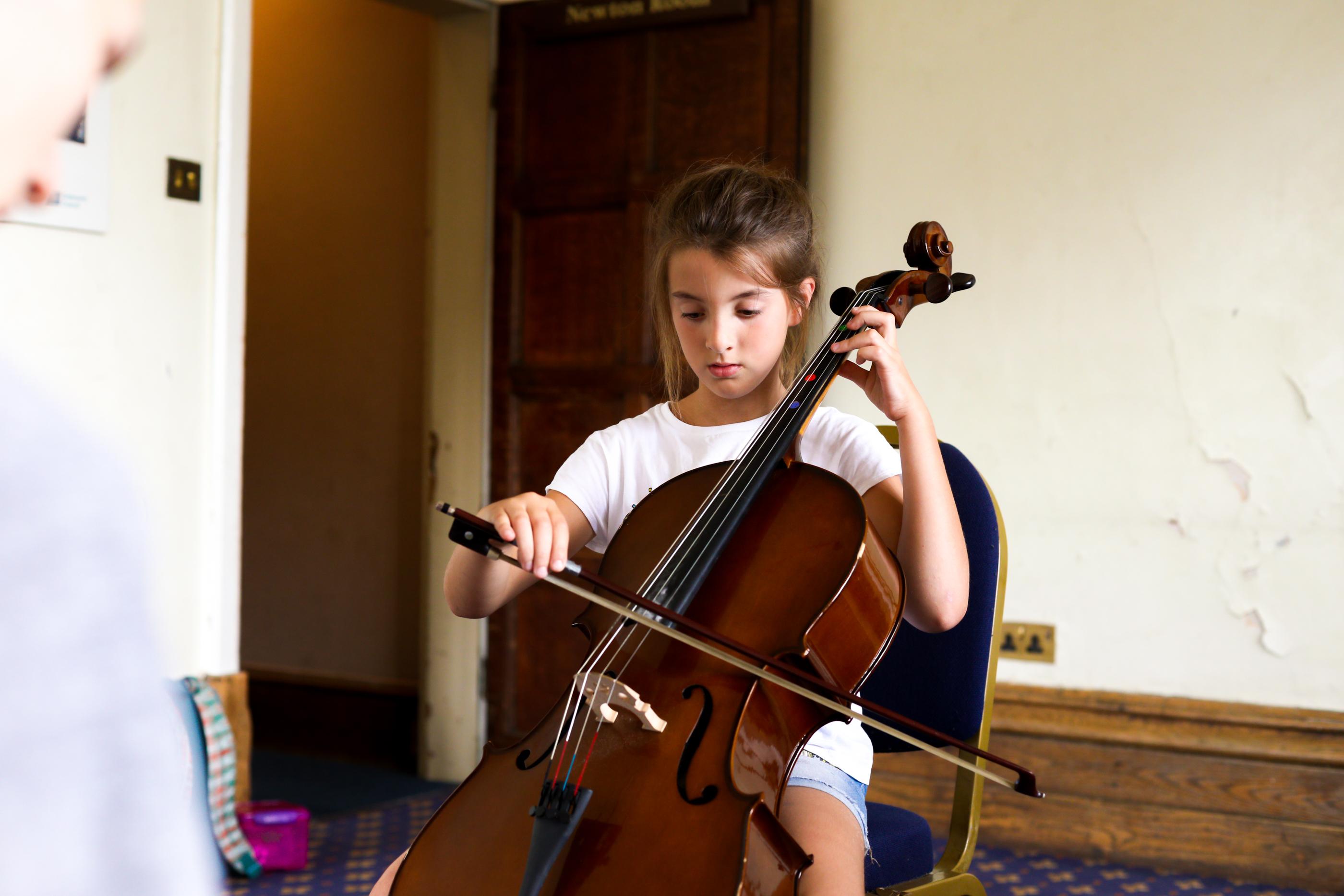 A photograph of a girl playing a cello