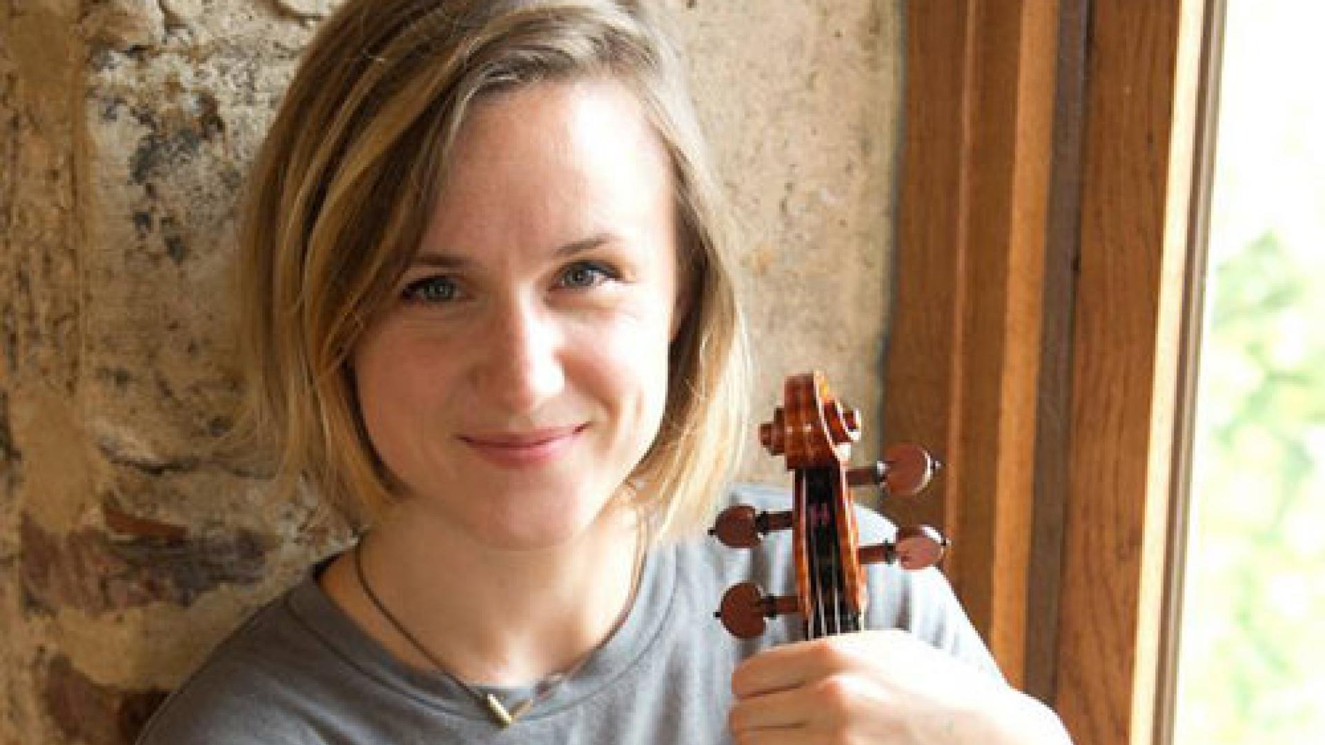 A closeup photograph of Naomi Burrell holding a violin