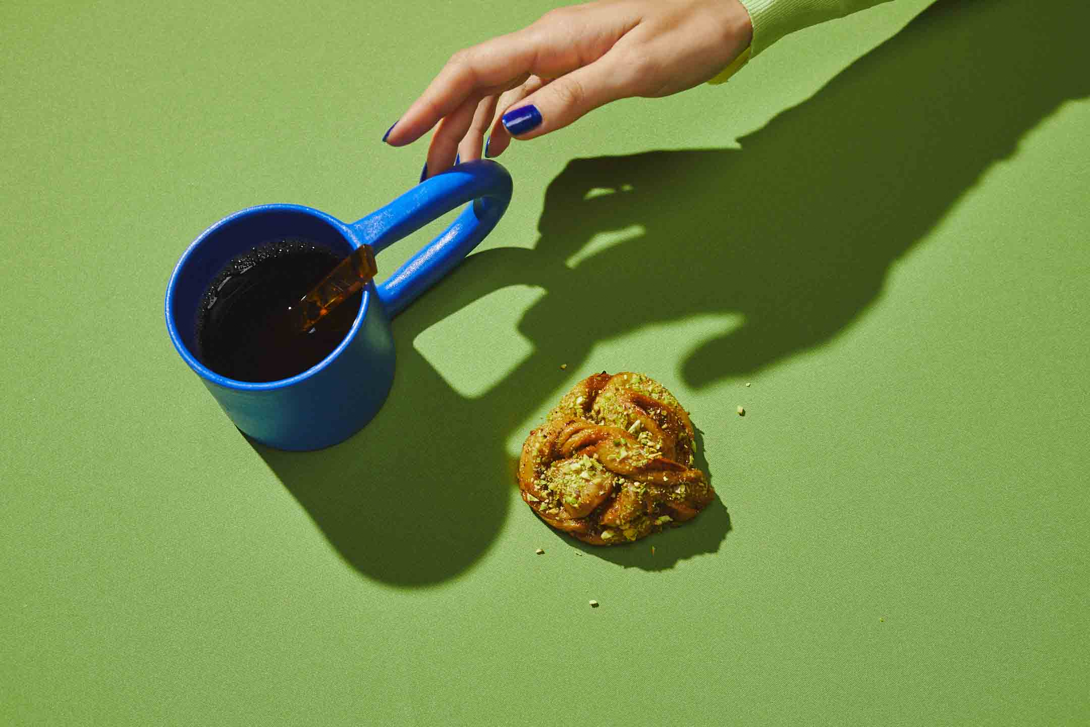 hand reaching for a cup of coffee next to a pastry on a bright lime green background.