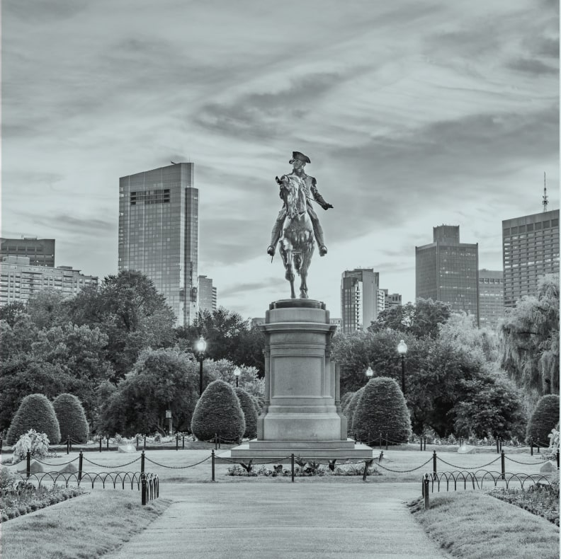a statue of a colonial era soldier riding a horse in the middle of a park in the city of Boston