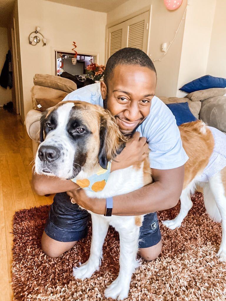 Man squatting down to huge large dog looking at camera