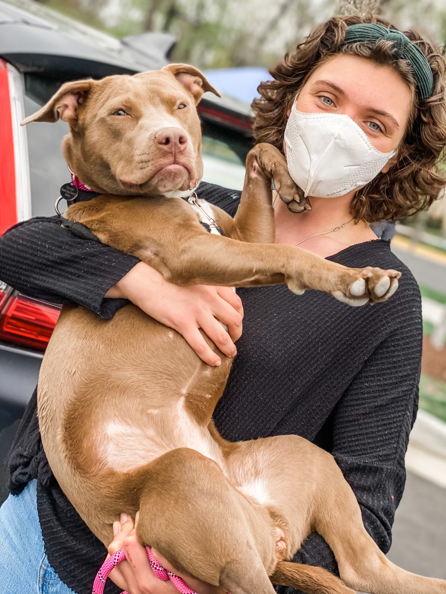 The Little Black Dog co-founder wearing mask and holding tan dog in her arms
