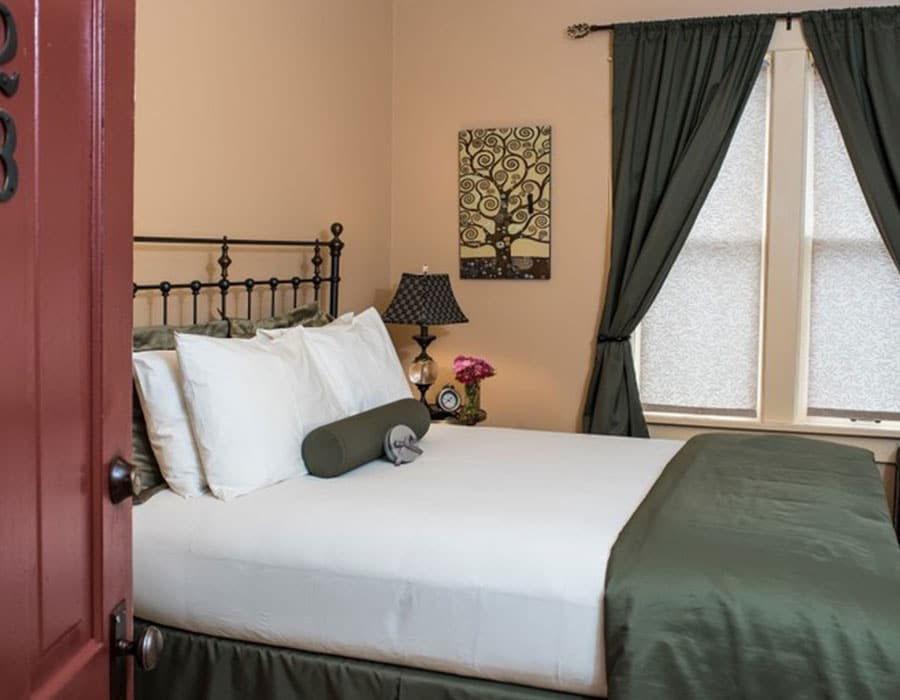 Queen suite bed at the Chamberlin inn, Cody Wyoming