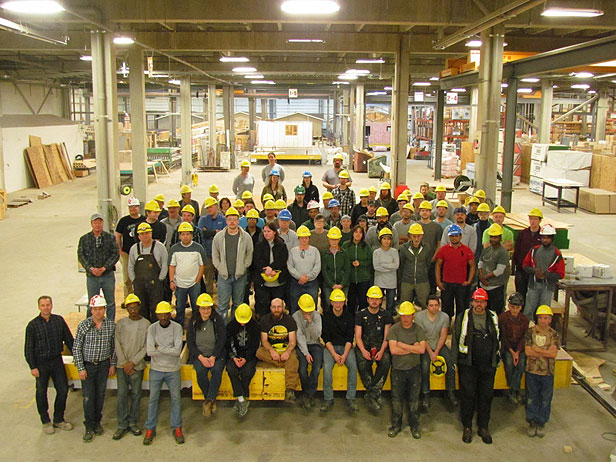 MODSOLID factory employees all standing in a group smiling