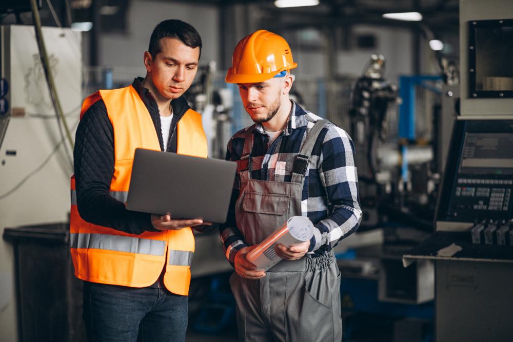 Photo de deux hommes contrôlant des installations mécaniques.