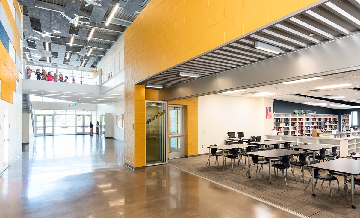 Aviation inspired graphics hang from above with the library and learning lab open to the atrium.