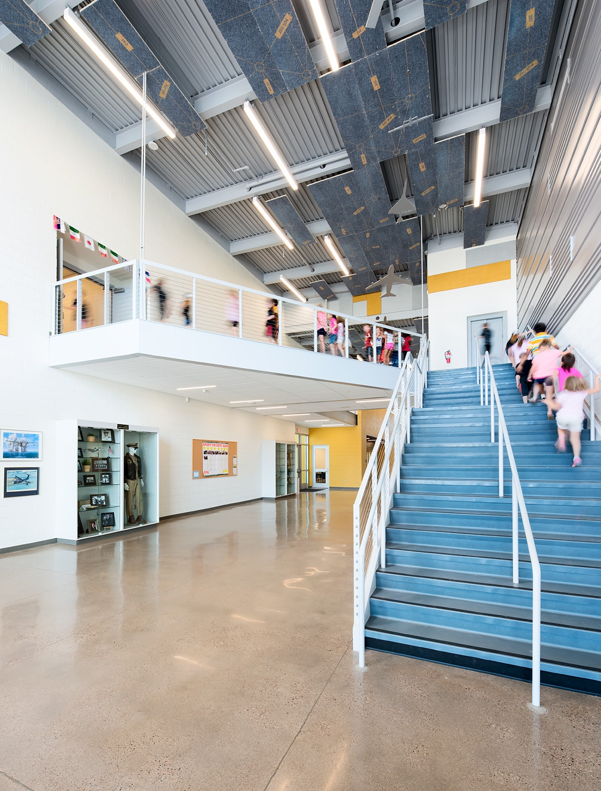 Entering the school atrium, replicated flight patterns tessellate on custom printed ceiling tiles with scale model planes suspended from the ceiling. Each model plane represents a milestone in aviation history moving from early flight to modern-day flight through the space.