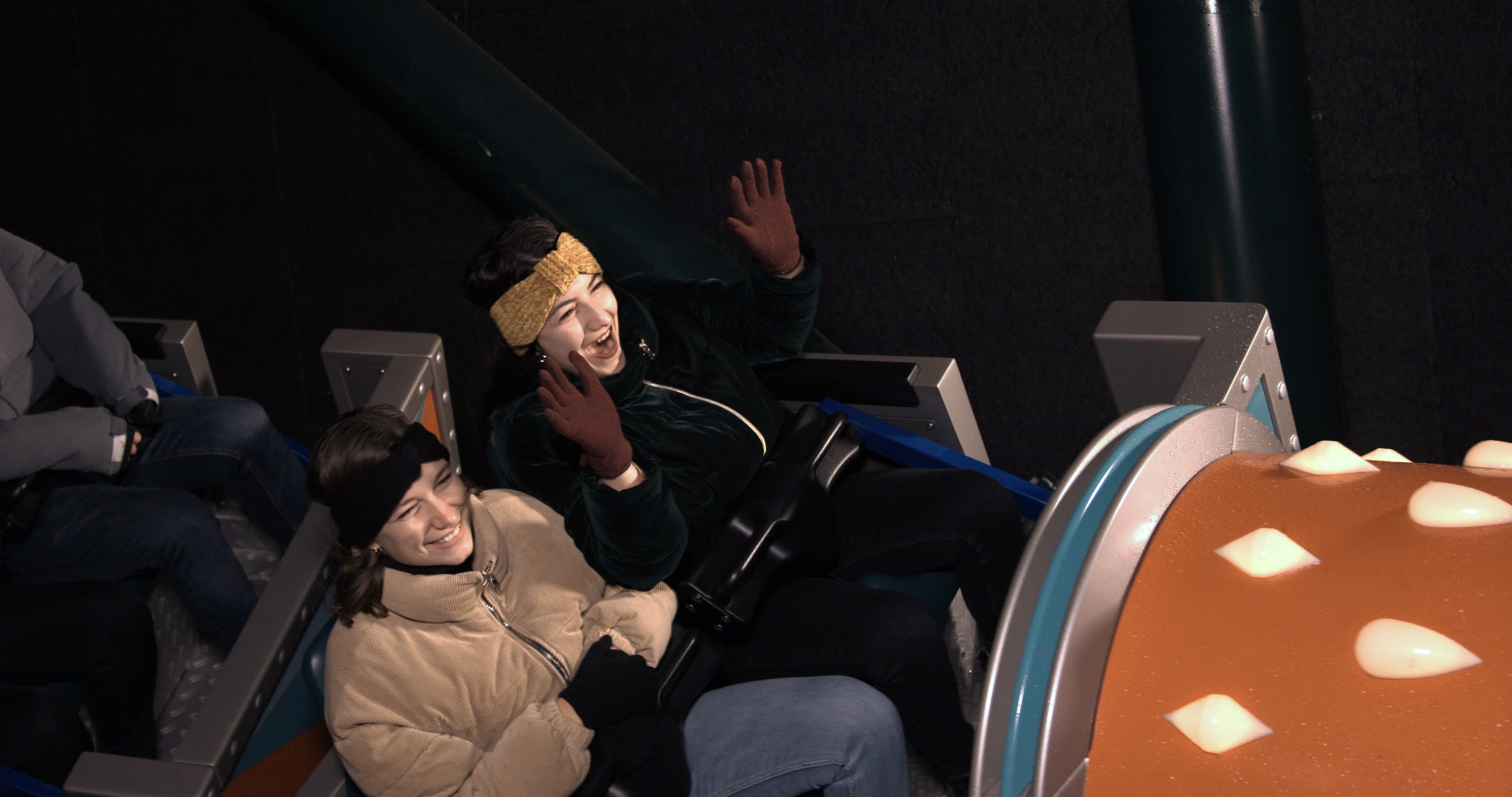 Two people riding a rollercoaster and smiling raising their hands up