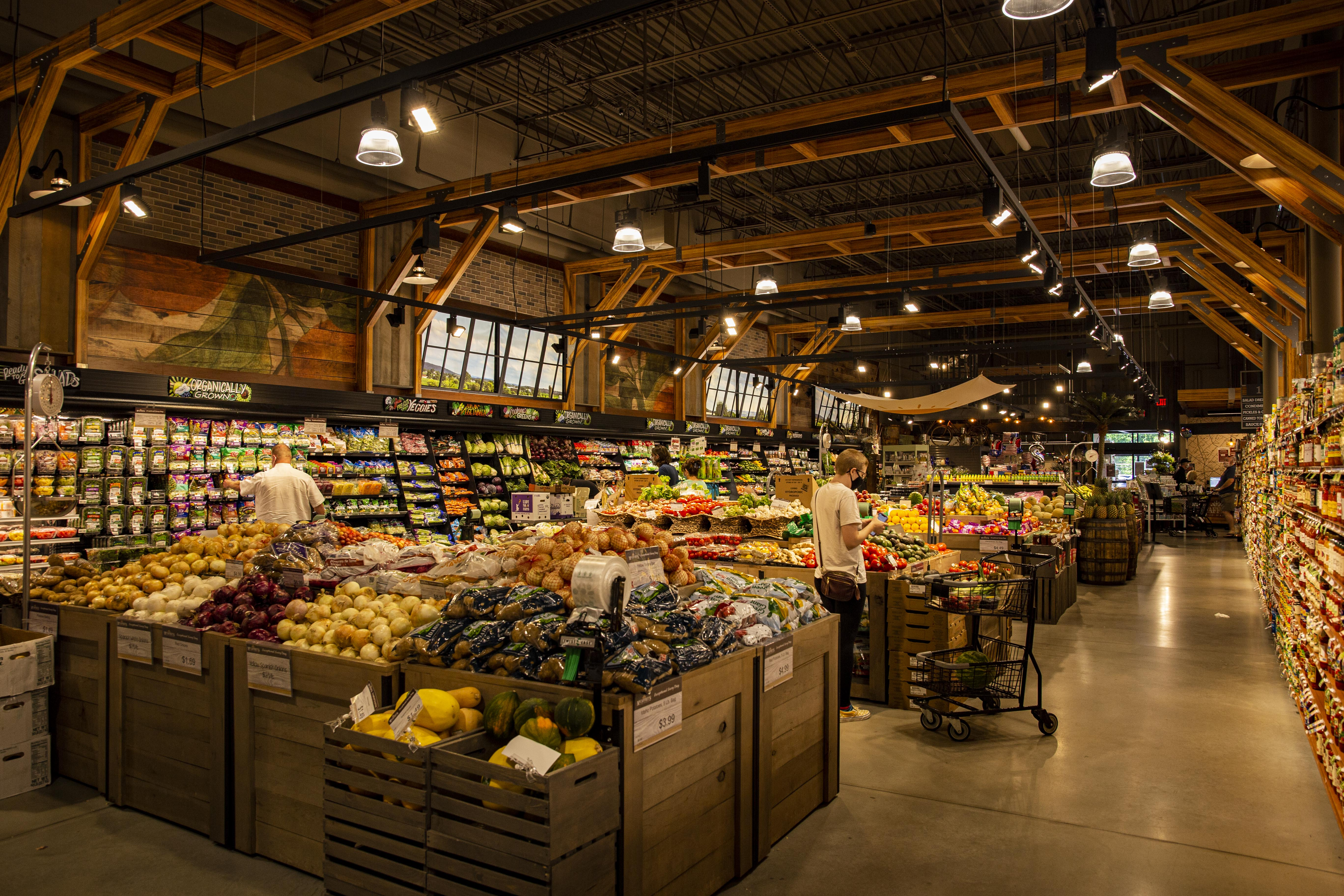 Interior of supermarket, fruits and vegetable section. Two people browsing with shopping carts.