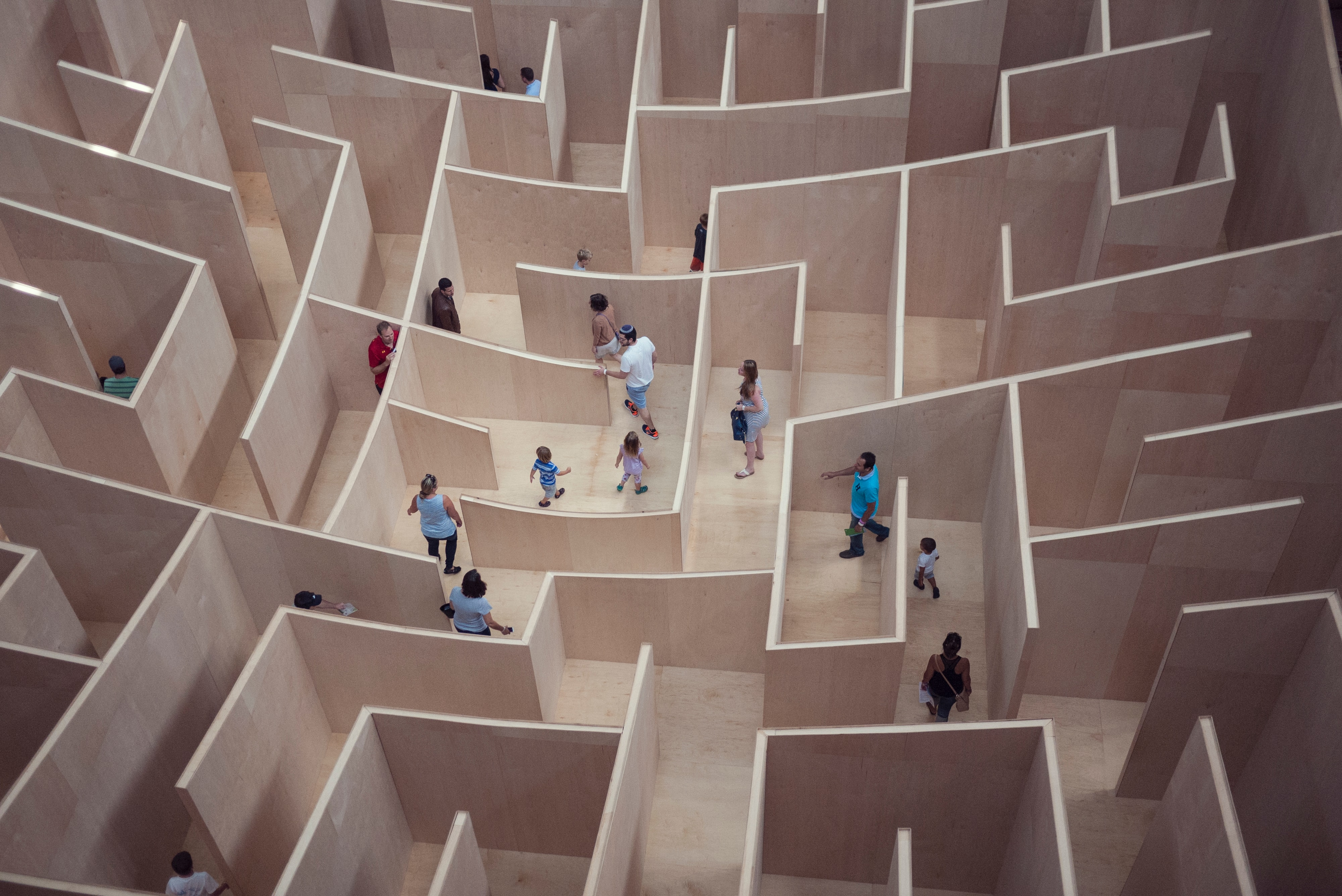 Overhead view of a wooden maze with people walking through it