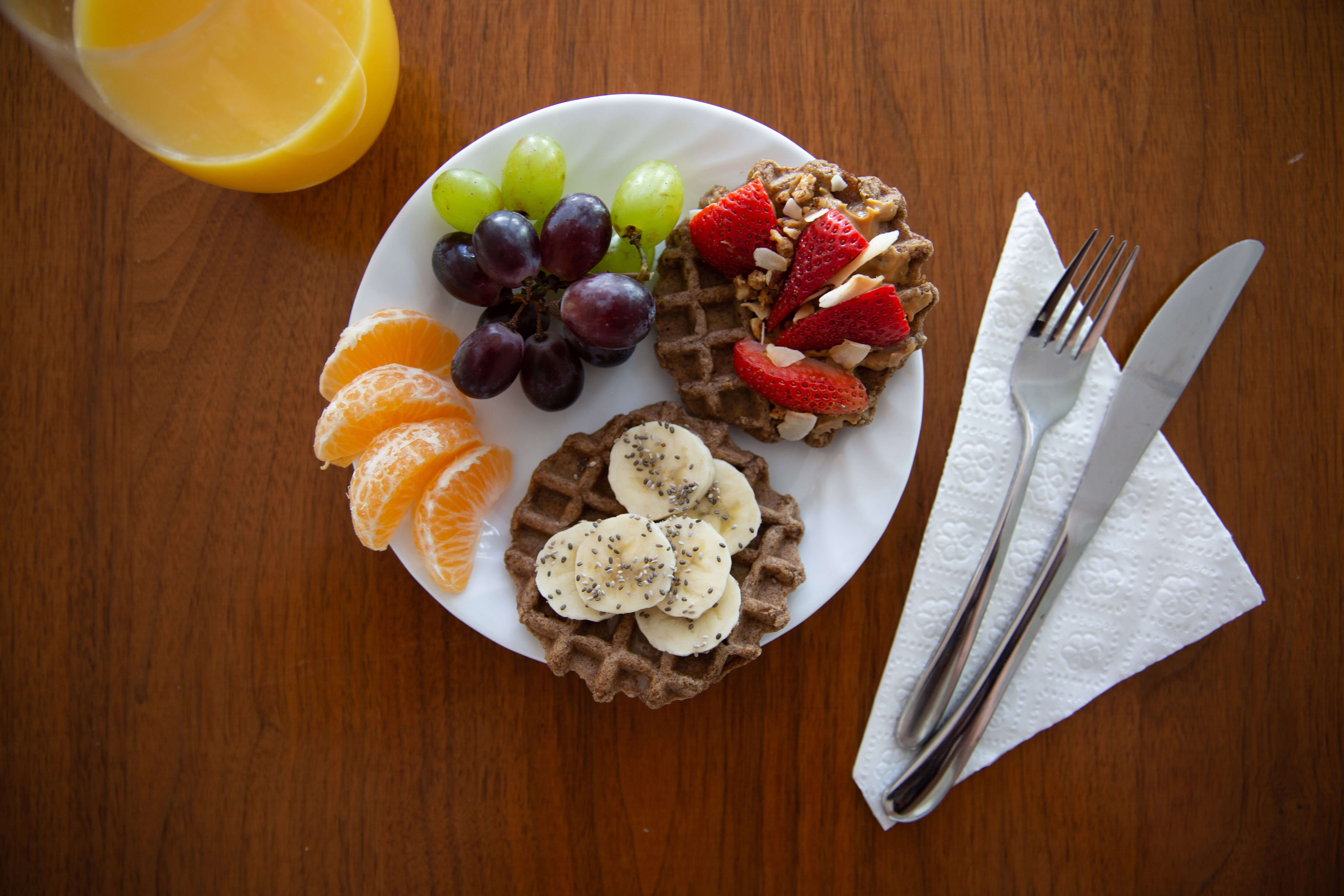 Breakfast picture of waffles, fruit, OJ, and utensils