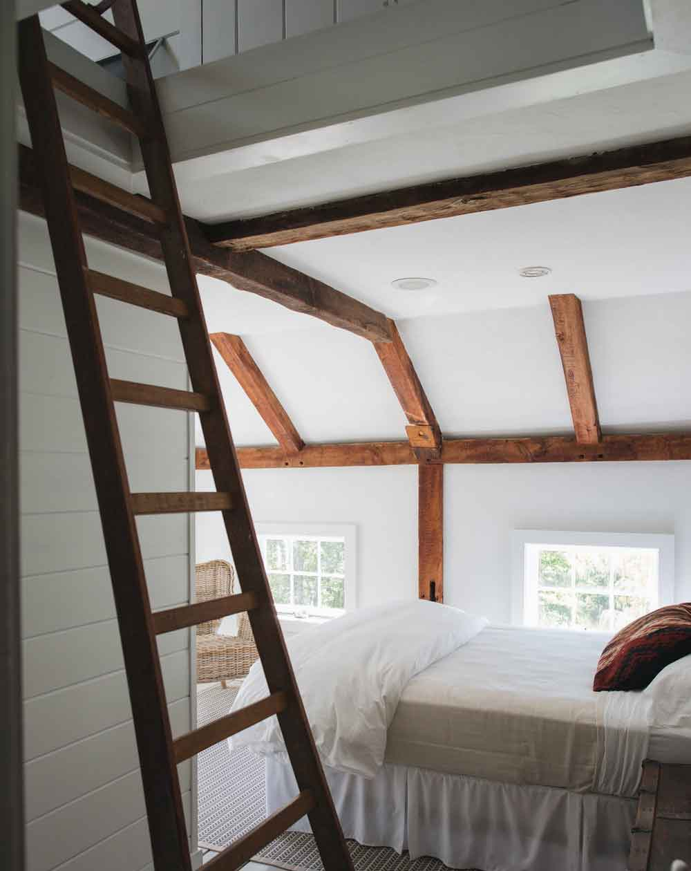 The Mary Margaret Room, which overlooks the back lawn, is located on the second floor of what was originally a small attached barn. It has a cozy loft area with two twin beds, accessible only by an antique French fruit ladder (suitable for children over age 6). This airy room features a queen bed, two twin beds, and a compact en suite bathroom with a walk-in shower.