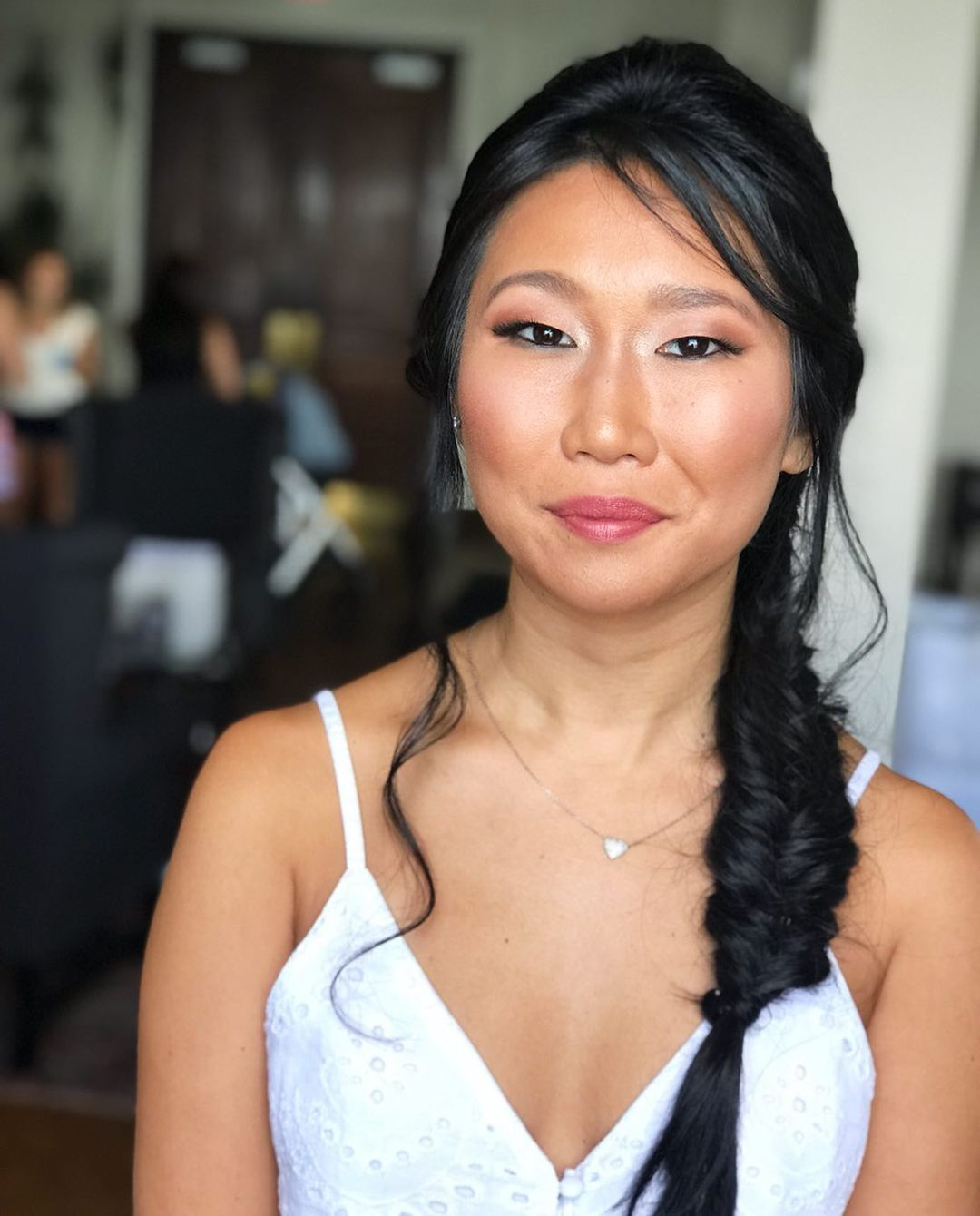 Bride smiling with simple, glowy makeup done and fishtail side braid.