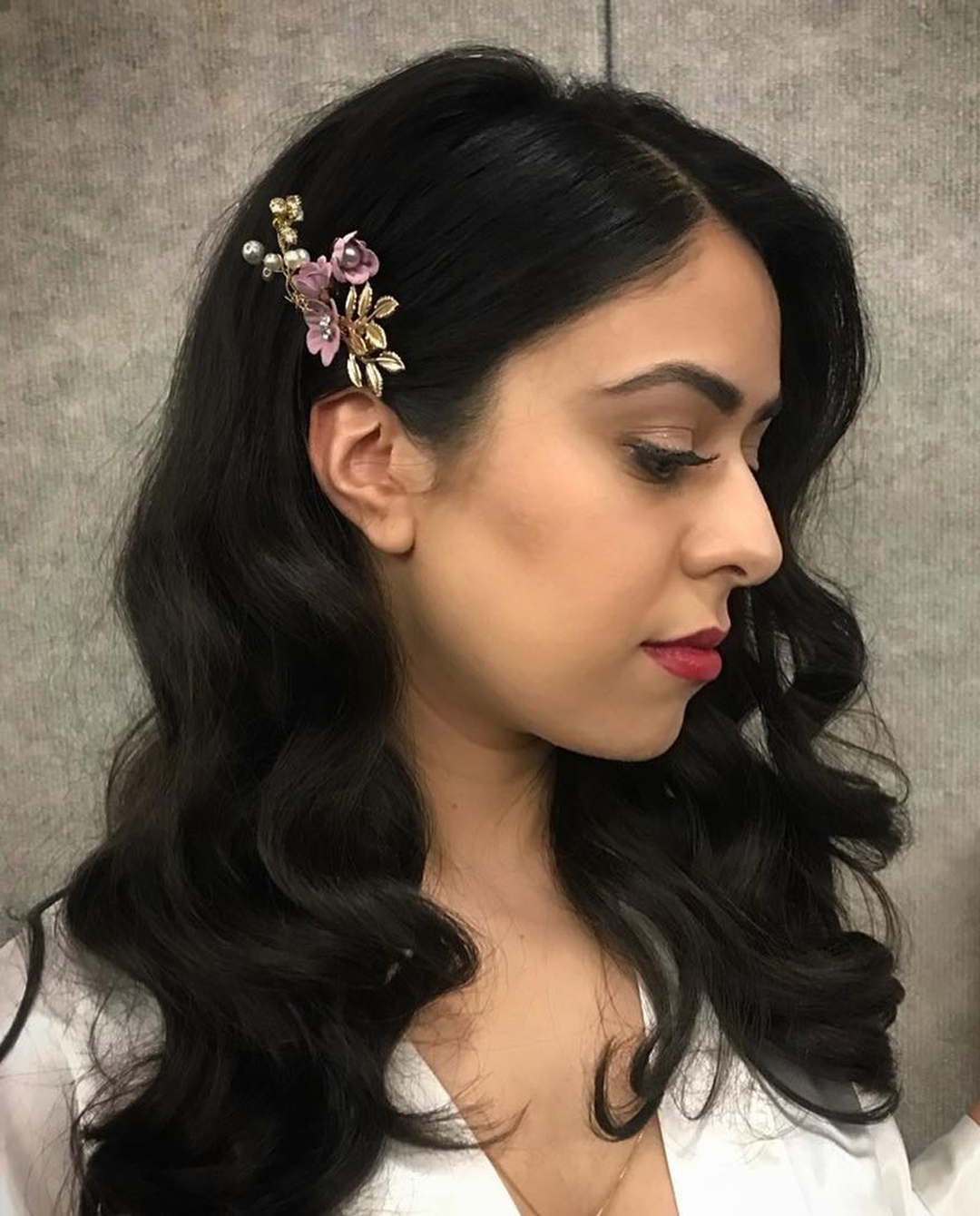 Woman with wavy hair styled to the side with a barrette