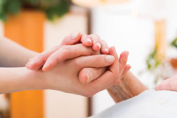 Younger person holding hands of elderly individual.