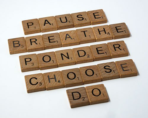 Scrabble pieces spelling out pause, breathe, ponder, choose, and do