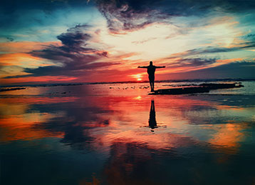 Person with arms out enjoying the sunset over a body of water