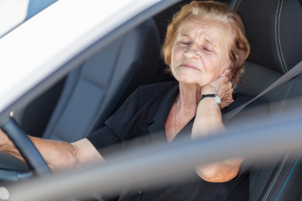 women in car holding her neck