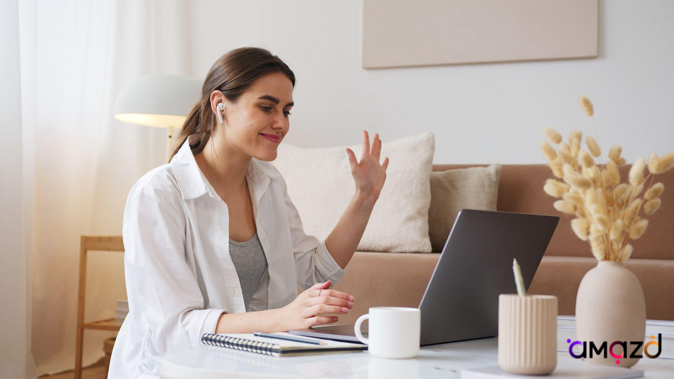A happy woman having a video call on their computer with a product expert on AMAZD.