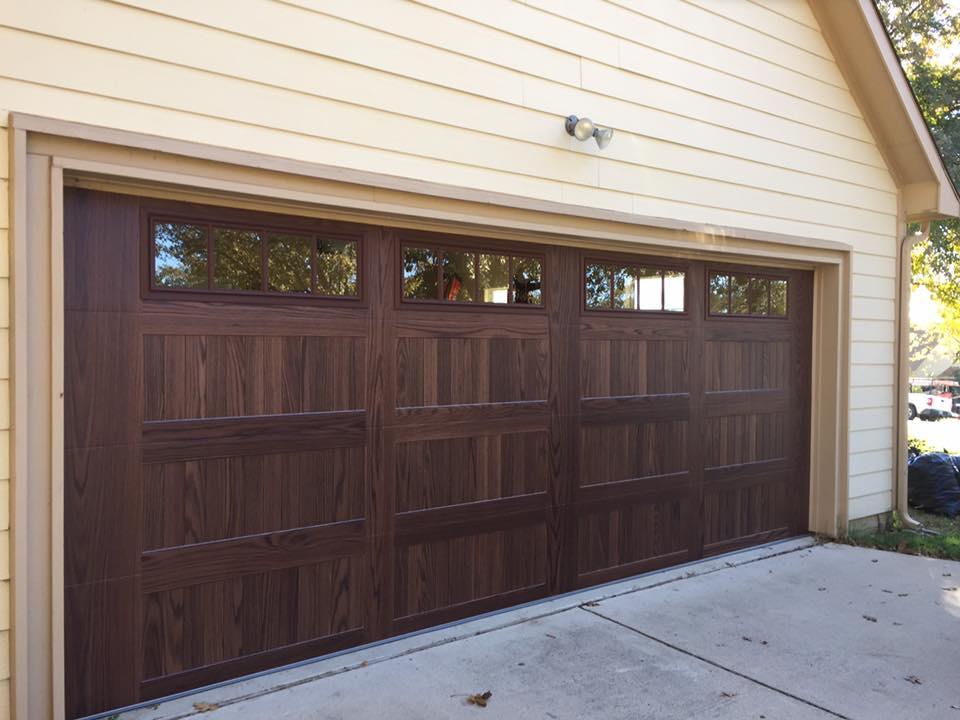 wood looking metal garage door with window panels at the top of the door