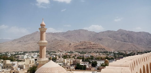 Top View from the NIzwa Fort in Oman with Mountains and a Mosque upfront.