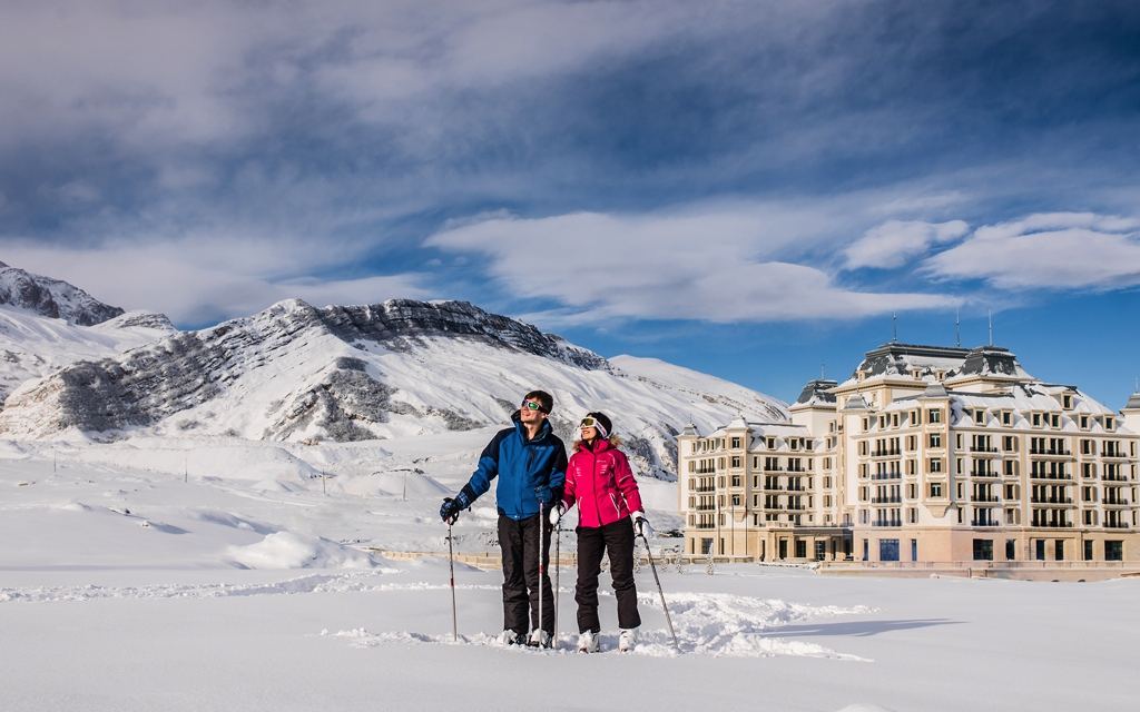 skiers in front of ski hotel and snow covered landscape