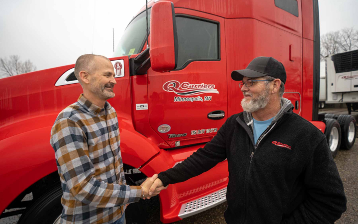 two men shaking hands next to a red truck