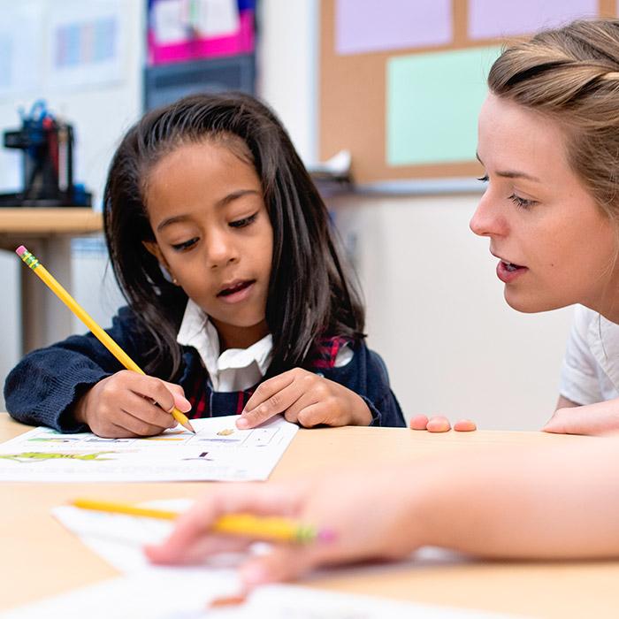 Geneva School teacher talking to student at desk while writing