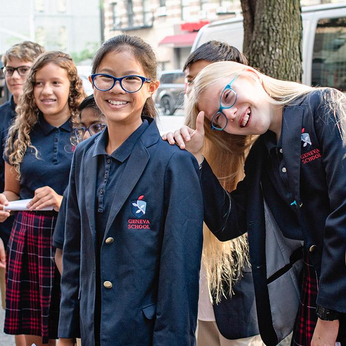 Geneva School students in uniforms smiling outside
