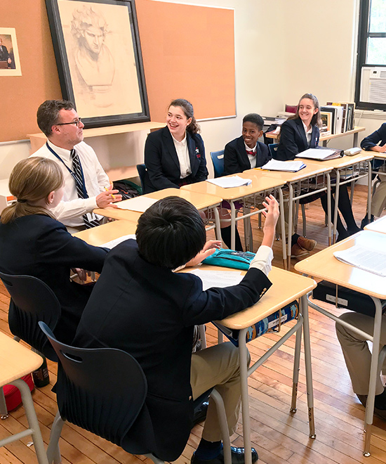 Upper School students sitting in a circle of desks