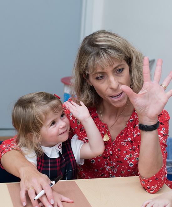 Geneva School teacher showing how to count on your fingers to preschool girl