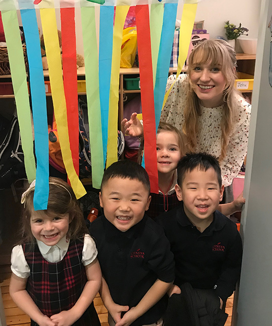 Young Geneva School students smiling under streamers with teacher