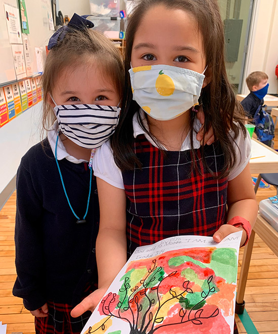 Two Geneva School students wearing masks showing painted artwork of a tree